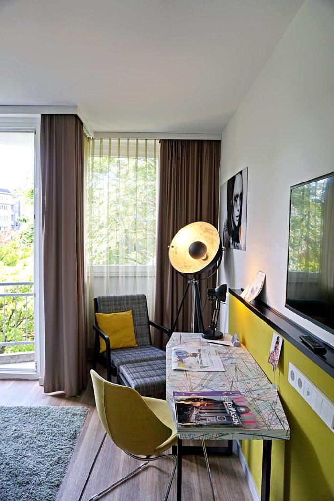 Design Hotel Indigo Düsseldorf - Hotel Düsseldorf Altstadt - Zimmer Schlafzimmer Schreibtisch Ausblick Kunst Balkon
